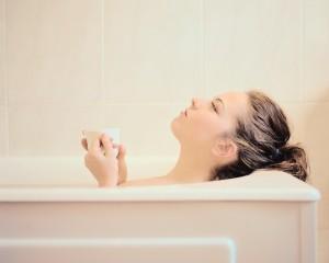 Woman Lying in a Bathtub Holding a Mug